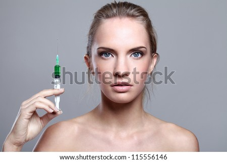 Beautiful woman and syringe with green liquid over gray background - stock photo