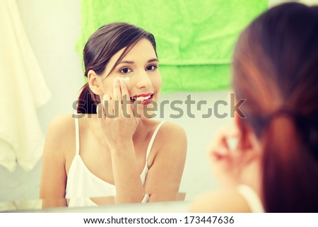 Beautiful woman applying cream on face at bathroom - stock photo