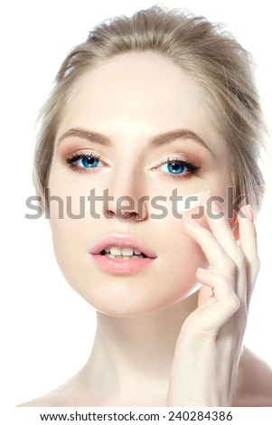 Beautiful woman applying cream on her face - stock photo