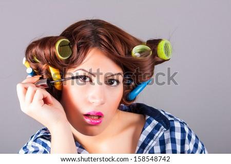 beautiful woman applying eyeliner - stock photo