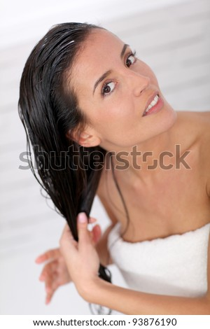 Beautiful woman applying hair conditioner - stock photo
