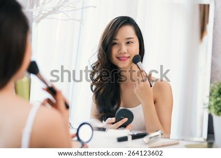 Beautiful woman applying make-up at the dressing table