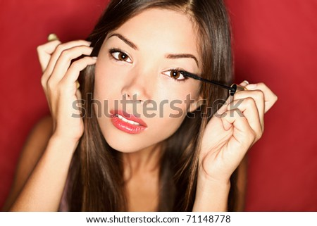Beautiful woman applying mascara at party. Asian woman getting ready putting makeup on eyes. - stock photo