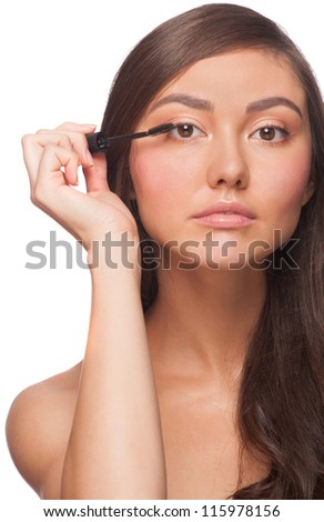 Beautiful woman applying mascara on her eyelashes, isolated on white background - stock photo