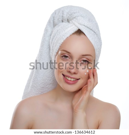 Beautiful woman applying moisturizer cosmetic cream on face over white background