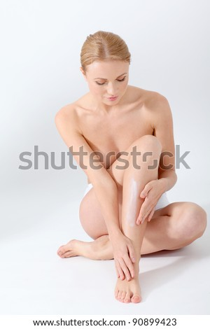 Beautiful woman applying moisturizer on her legs - stock photo