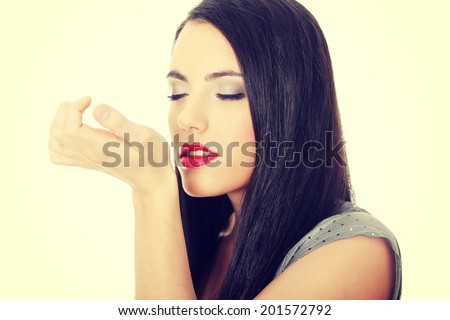 Beautiful woman applying perfume on her body, bright red perfume bottle - stock photo