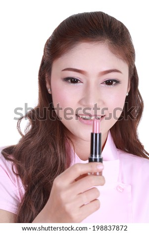 Beautiful woman applying pink lipstick isolated on white background
