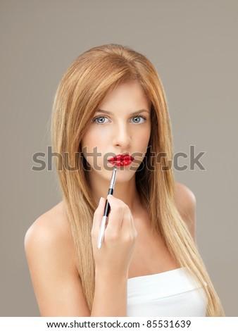 beautiful woman applying red lipstick with brush - stock photo