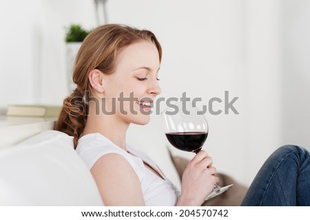 Beautiful woman appreciating a glass of red wine smiling with satisfaction as she looks down at the glass tilted in her hands while enjoying a quiet evening at home - stock photo