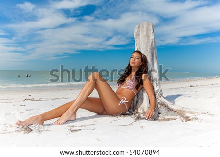 Beautiful woman at a beach, sitting in the sand - stock photo