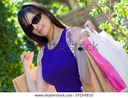 Beautiful woman at a shopping center with bags - stock photo