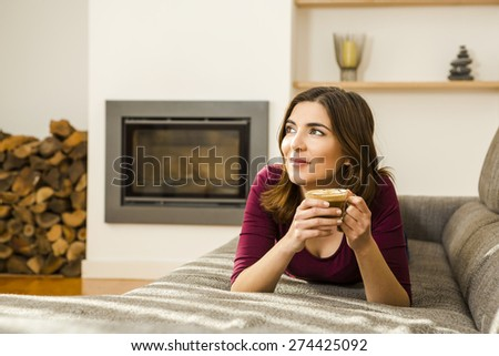 Beautiful woman at home drinking a capuchino - stock photo