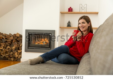 Beautiful woman at home drinking a coffee at the fireplace