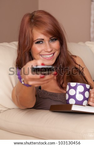 Beautiful woman at home holding TV remote and laughing - stock photo