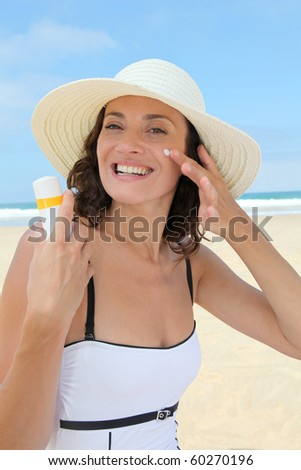Beautiful woman at the beach putting sunscreen on her body - stock photo