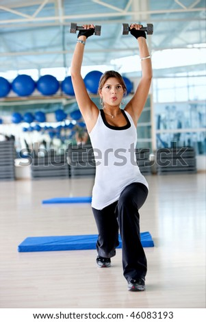 beautiful woman at the gym exercising with free weights