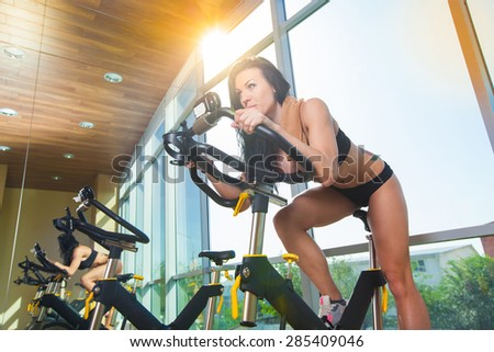 Beautiful woman at the gym on bike, cycle, sunny gym, general plan - stock photo