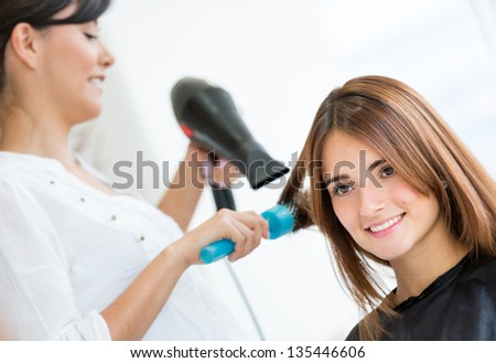Beautiful woman at the hair salon blow drying her hair