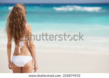 Beautiful Woman At Tropical Beach. Back View. - stock photo