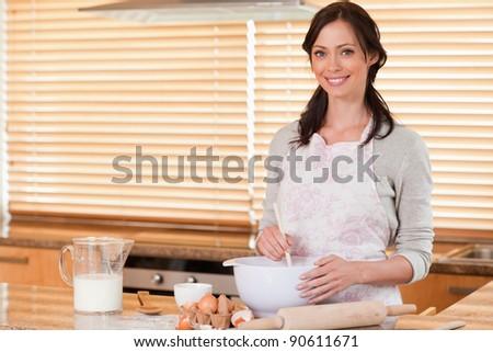 Beautiful woman baking in her kitchen - stock photo