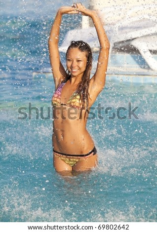 Beautiful woman bathes in pool under water splashes - stock photo