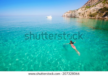 Beautiful woman bathing in clear sea. Active vacation on the beach. - stock photo