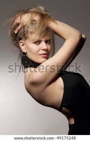 beautiful woman bending back in sexy evening dress against dark background - stock photo