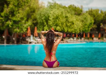 Beautiful woman bikini at swimming pool, summer vacation. - stock photo