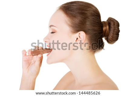 Beautiful woman biting a chocolate bar. Isolated on white - stock photo