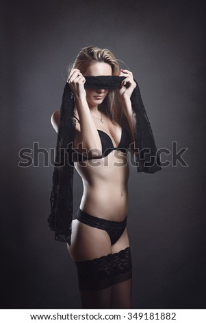 Beautiful woman blindfolded with black silk. Passion and seduction