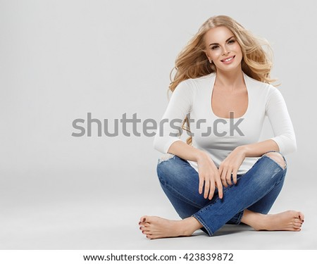 Beautiful woman blonde curly hair sexy portrait jeans fashion full length sitting on floor