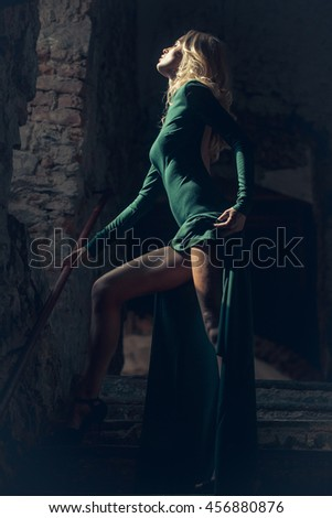 Beautiful woman blonde with long sexy legs dressed in beautiful vogue green dress posing on stone stairs on dark background indoor