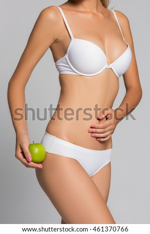 Beautiful woman body and green apple. Conceptual image of dieting healthy. Fashin and beauty