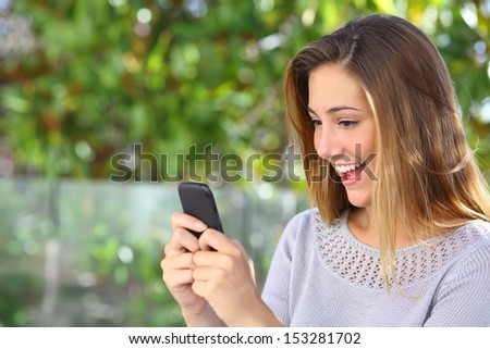 Beautiful woman browsing internet happy in her smart phone with a green background                - stock photo