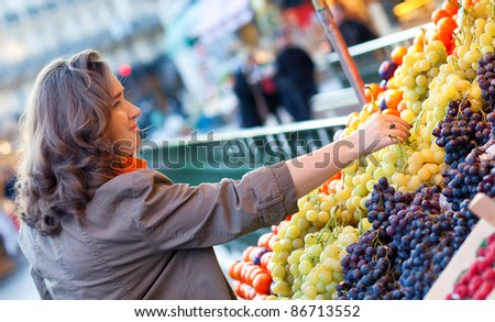Beautiful woman buying grapes at market