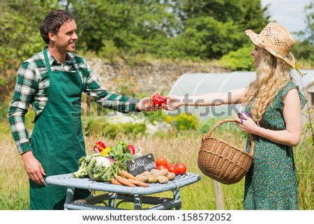 Beautiful woman buying vegetables at farmers stall from a young farmer - stock photo