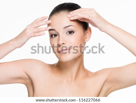 Beautiful woman cares of forehead - posing at studio  isolated on white - stock photo