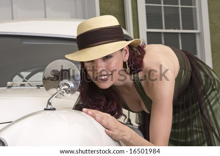Beautiful woman checking out her look in the sideview mirror of a classic Jaguar car - stock photo