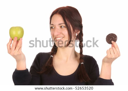 beautiful woman choosing between apple and chocolate cookies on white background - stock photo