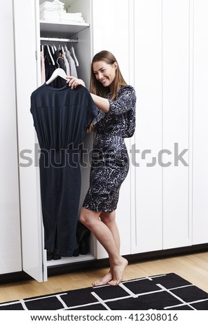 Beautiful woman choosing dress from closet