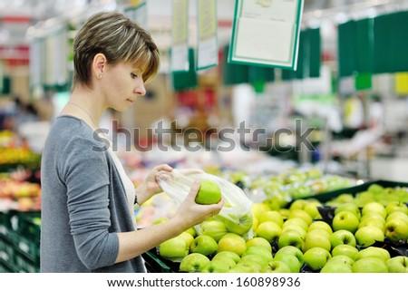 beautiful woman choosing green apple during shopping at fruit vegetable supermarket - stock photo