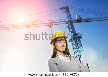 beautiful woman civil engineer smiling with confidence in front of a crane in a sunset flare background - stock photo