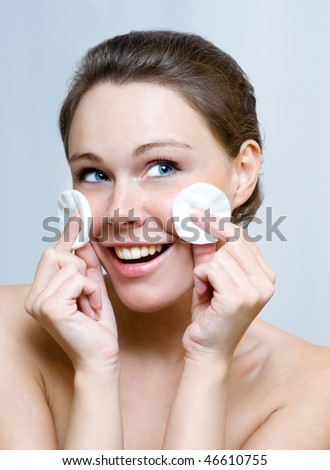 Beautiful woman cleaning face by cotton pad - stock photo