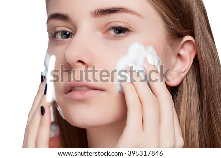 Beautiful woman cleaning her face with a foam treatment on a white light background. Beauty Portrait. Beautiful Spa Woman Smiling. Perfect Fresh Skin. Pure Beauty Model. Youth and Skin Care Concept - stock photo