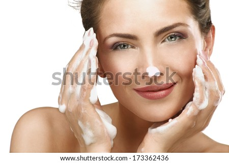 Beautiful woman cleaning her face with a foam treatment on white - stock photo