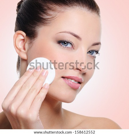 Beautiful woman cleaning her face with cotton swab - over white background