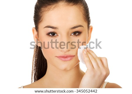 Beautiful woman cleaning make up with cotton pad. - stock photo