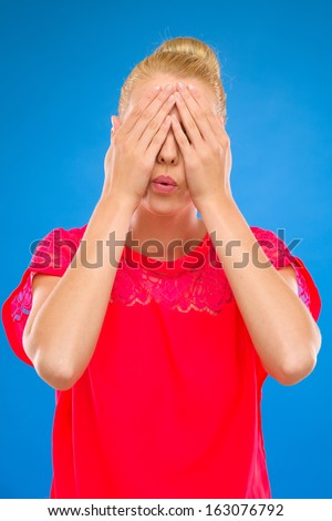 Beautiful woman closes her eyes. Studio shot isolated on blue. - stock photo