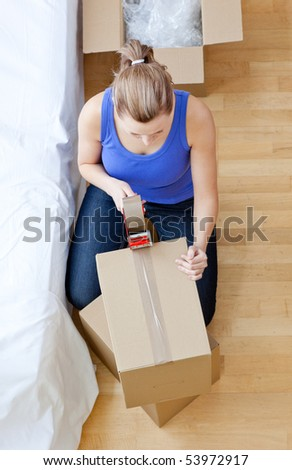 Beautiful woman closing a box at home